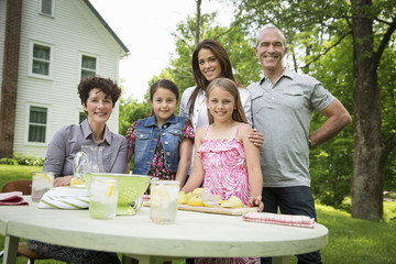 A Summer Family Gathering At A Farm. Five People Posing Beside The Table, Where A Child Is Making Fresh Lemonade.