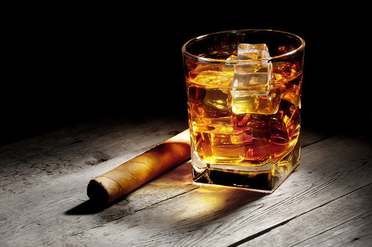 Glass of whiskey with a cigar
