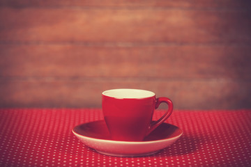 Cup of a coffee on polka dot cover.