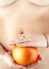 Close-up of female hands holding an orange in front of belly