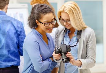 two women looking at digital camera at office