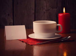 cup of coffee, candle and paper on wooden background