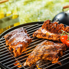 Grilling marinated ribs on a portable BBQ