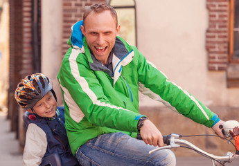 Father with little son cycling together