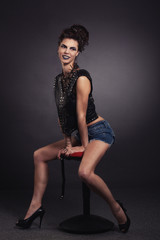 creative sexy girl in a black vest sits on a chair