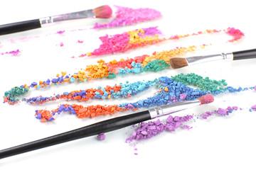 Crushed eyeshadow and professional make-up brush close up