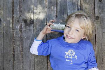 Deutschland, Köln, Junge zu hören Büchse Telefon
