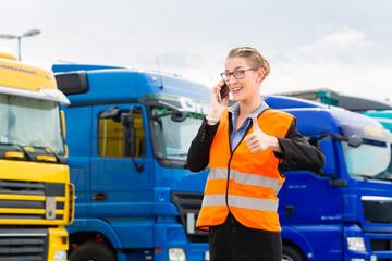 Fototapete - Spediteurin vor Lastwagen und LKW auf Depot