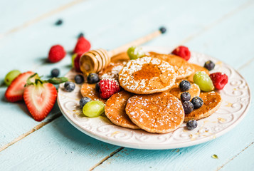 Pancakes with berries on wooden background