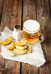 Beer mug and potato wedges on rustic wood table