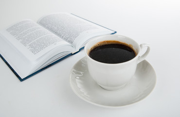 cup of coffee with open book on white