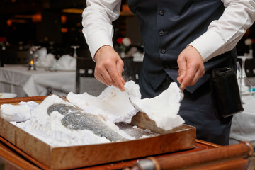 Waiter is carving fish baked in salt crust
