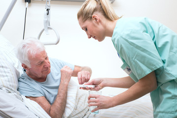 Senior mit Pflegerin im Altenheim Medikamenteneinnahme