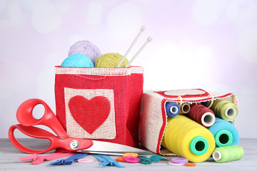 Bags with bobbins of colorful thread and woolen balls