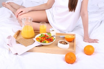 Woman in bed with light breakfast