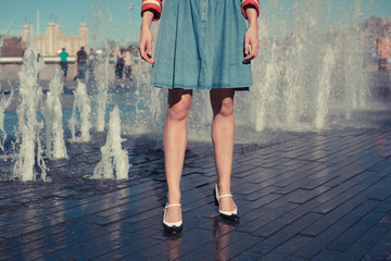 Young woman standing by fountain in city on a hot day