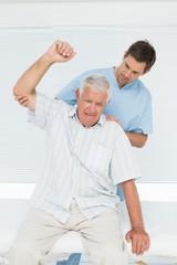 Mhysiotherapist assisting senior man to raise hand