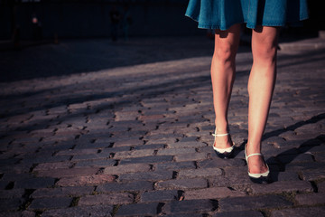 Young woman in skirt walking on a cobbled street