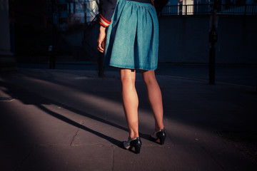 Young woman standing in the street at sunset