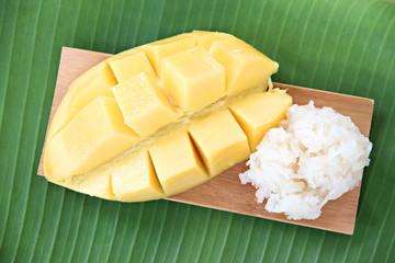 Ripe mango and sticky rice in bamboo dish on banana leaves.
