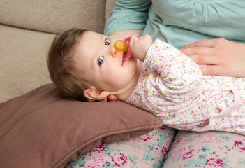 Baby playing with pacifier lying over mother legs