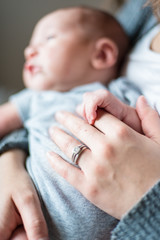 Selective focus hand detail of a baby boy and mother bonding