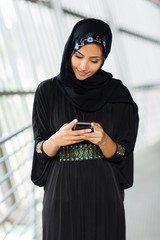 muslim woman reading email on smart phone