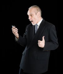 Happy businessman wearing a black suit, smiling and reading sms on mobile phone, with thumb up, on black background