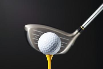 Golf club and ball on tee.