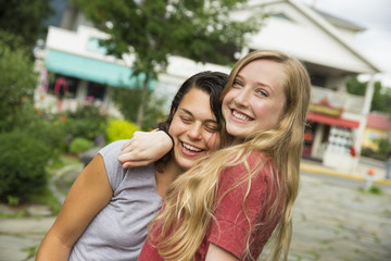 Two girls hugging and laughing.