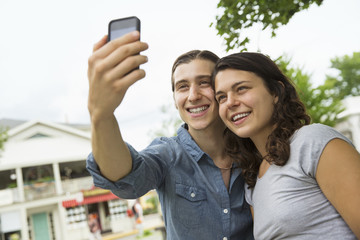 A young couple side by side, flirting and taking photographs.
