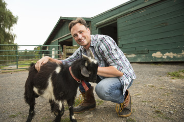 An organic farm in the Catskills. A man with a small goat on a halter.