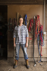 An organic farm in the Catskills. A man standing in a tack room in a stable.
