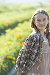 Summer on an organic farm. A young girl in a field of flowers.