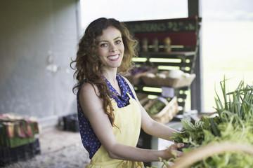 An organic farm stand. A woman sorting vegetables.