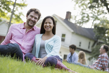 A couple sitting on the grass at a summer party.