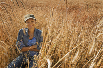 A woman sitting smiling in a field of tall ripening cereal crop, corn or wheat.
