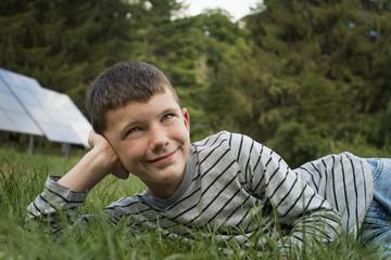 A boy lying in the grass, beside solar panels.