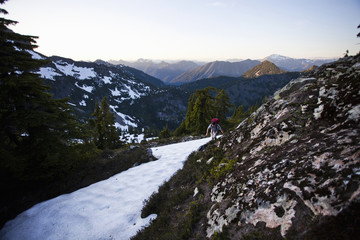 A young man scrambles around a snow patch while hiking to the summit of a large mountain in the Cascades of Washington, USA.