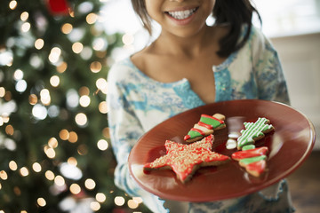 A young girl holding a plate of organic decorated Christmas cookies.
