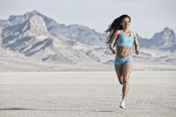 A young woman running through the landscape on the salt flats surface near Salt Lake city.