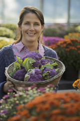 A woman holding a bowl of fresh produce, purple sprouting broccoli. Flowering plants. Crysanthemums.