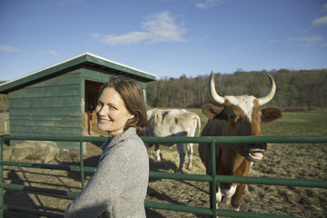 Animal sanctuary. A woman beside the fence, feeding two cows.