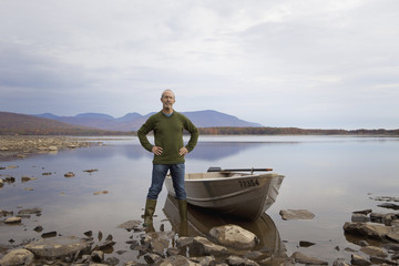 A man standing on a lake shore beside a small rowing boat.