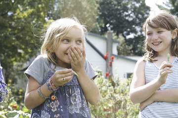 Two children standing outdoors in a garden laughing.