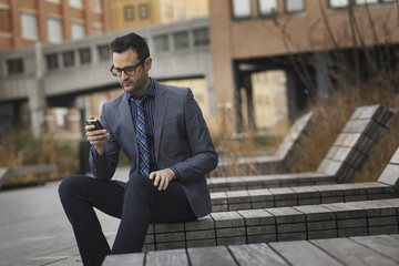 A man in a formal jacket and tie, sitting on a bench outside a city building, checking his phone for messages.
