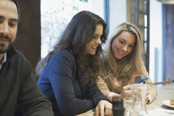 Women sharing text at restaurant table