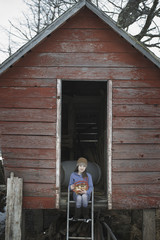 An organic farm in upstate New York, in winter. A girl sitting on the ladder of a henhouse with a basket of eggs.