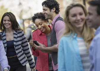 People outdoors in the city in spring time. A group of men and women, two looking at a cell phone screen and laughing. Wall mural