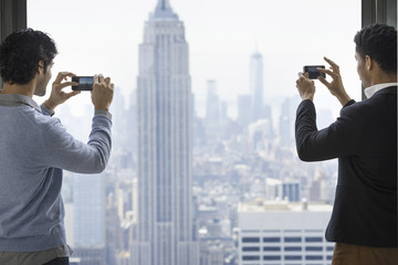 Urban lifestyle. Two young men using their phones to take images of the city from an observation platform overlooking the Empire State Building.